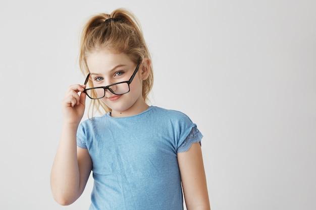 Linda garota loira pequena com olhos azuis e sorriso agradável em camiseta azul engraçado posando com óculos novos para foto de escola. Foto gratuita
