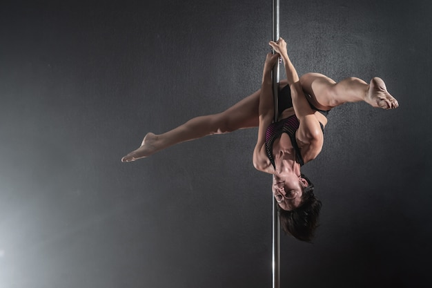 Linda garota magro com pilão feminino pole dancer dançando sobre um fundo preto Foto Premium