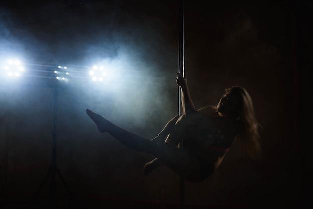 Linda garota magro com pilão. mulher de dançarina de pole feminino dançando em um poste Foto Premium