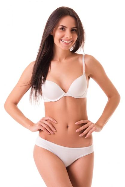 Linda garota magro em lingerie branca está olhando para a câmera. Foto Premium