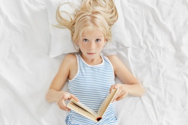 Linda garota, mantendo o livro nas mãos, lendo histórias interessantes enquanto estava deitado na cama, sendo surpreendida com um final inesperado. Foto gratuita