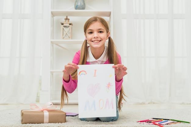 Linda garota mostrando desenho com eu amo a inscrição de mãe Foto gratuita