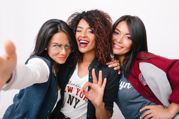 Linda garota mulata posando com sinal ok entre amigos latinos e asiáticos. retrato interno de mulheres jovens satisfeitas de diferentes países, juntas com sorrisos. Foto gratuita