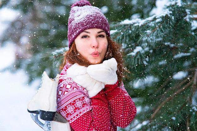 Linda garota, mulher manda um para mandar um beijo. mulher romântica, mulher segurando patins de inverno no ombro. atividades e esportes de inverno. Foto Premium