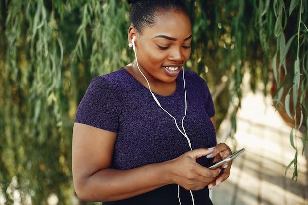 Linda garota negra em pé em um parque de sumer Foto gratuita