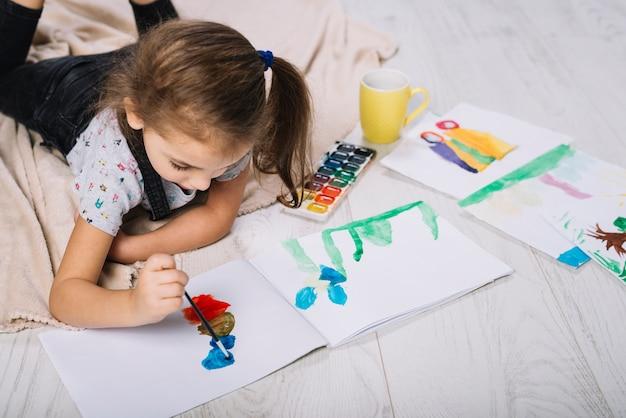 Linda garota pintando com aquarelle brilhante no chão Foto gratuita