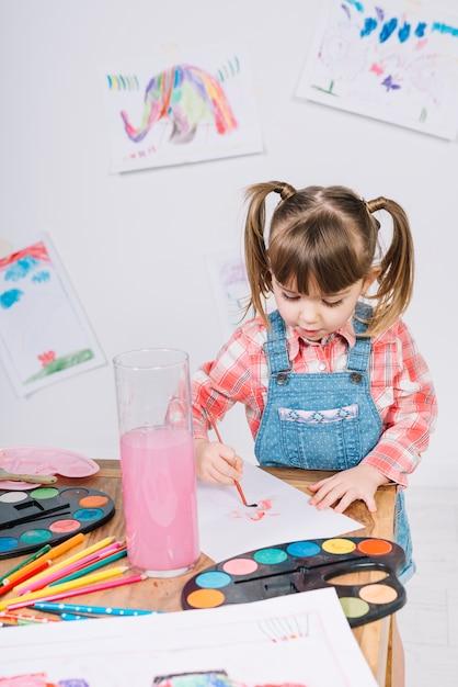 Linda garota pintando com aquarelle em papel Foto gratuita