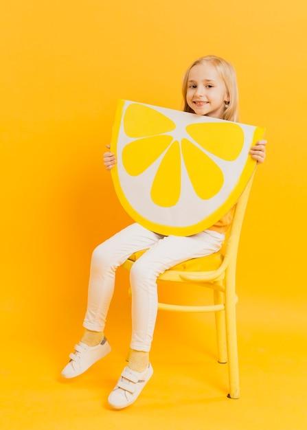 Linda garota posando enquanto segura a fatia de limão decoração Foto gratuita