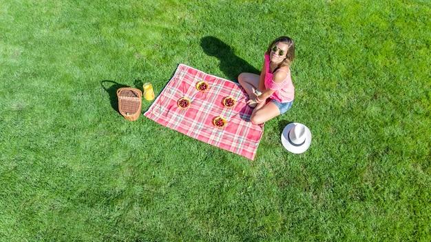 Linda garota relaxante na grama, fazendo piquenique de verão no parque ao ar livre, vista aérea zangão de cima Foto Premium