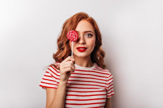 Linda garota ruiva com pirulito posando na parede branca. jovem atraente segurando bala vermelha. Foto gratuita