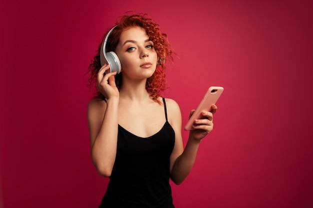 Linda garota ruiva em fones de ouvido brancos grandes com o telefone na mão, ouvindo música Foto Premium