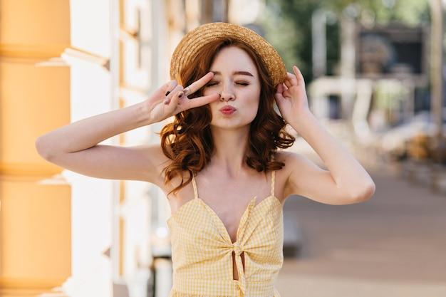 Linda garota ruiva em um vestido amarelo, posando com beijo de expressão facial na cidade. linda senhora encaracolada com chapéu de palha na moda, aproveitando o fim de semana de verão. Foto gratuita