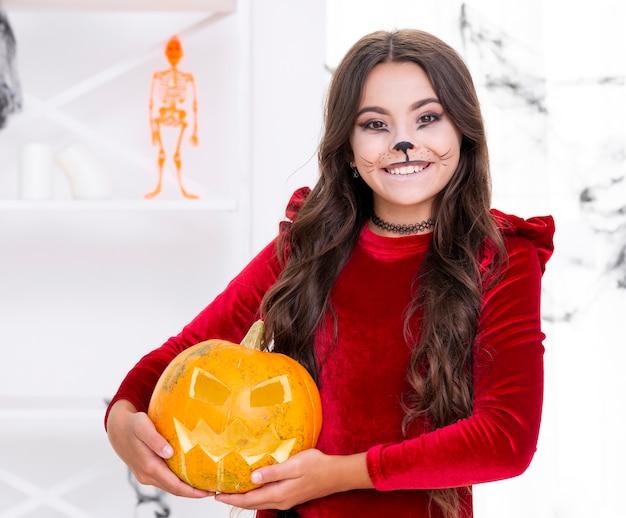 Linda garota segurando a abóbora de halloween mal Foto gratuita