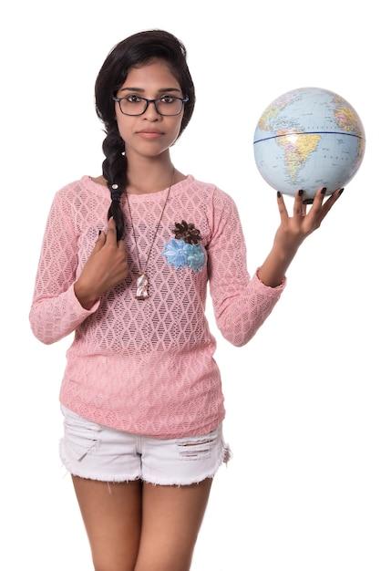 Linda garota segurando um globo terrestre isolado Foto Premium