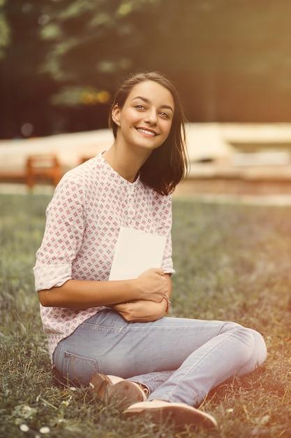 Linda garota segurando um livro aberto Foto gratuita