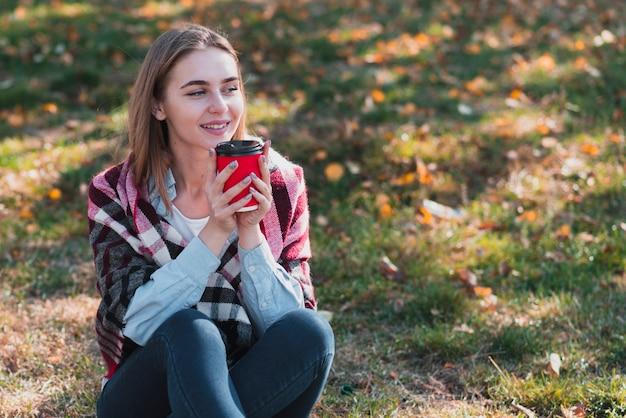 Linda garota segurando uma xícara de café e desviar o olhar Foto gratuita