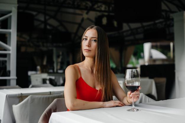 Linda garota senta-se e bebe vinho na varanda de uma casa bonita. feriado. Foto Premium