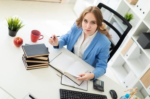 Linda garota sentada na mesa no escritório, segurando uma caneta na mão e lendo um livro. Foto Premium