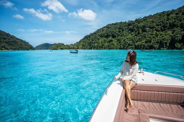 Linda garota sente-se no barco de cabeça velocidade e vendo o belo mar na ilha de surin, tailândia Foto Premium