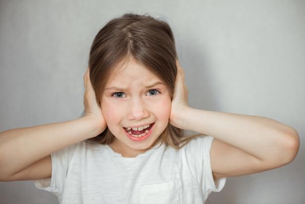 Linda garota sofrendo de dor de cabeça em fundo cinza Foto Premium