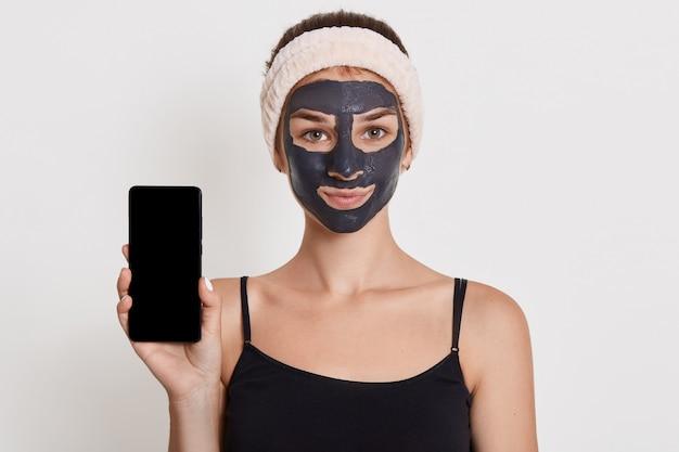 Linda garota sorridente com máscara preta no rosto, segurando o telefone inteligente com tela em branco, posando isolado sobre a parede branca senhora fazendo procedimentos de beleza em casa. Foto Premium