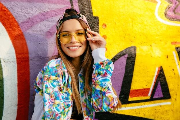 Linda garota sorridente em óculos, posando para a câmera. vestida com jaqueta elegante e boné. Foto gratuita