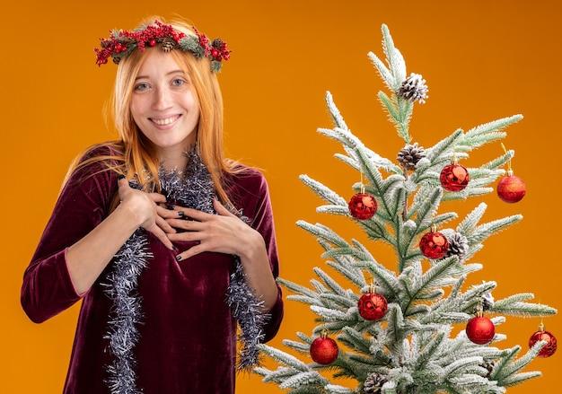Linda garota sorridente em pé perto da árvore de natal, usando um vestido vermelho e grinalda com uma guirlanda no pescoço, colocando as mãos em si mesma isolada em um fundo laranja Foto gratuita