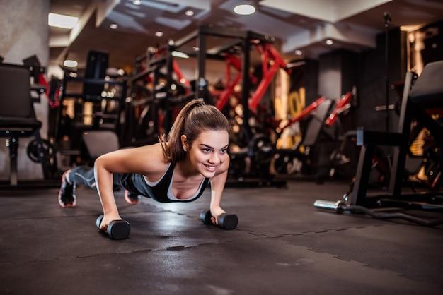 Linda garota sorridente fazendo push-up em pesos. Foto Premium