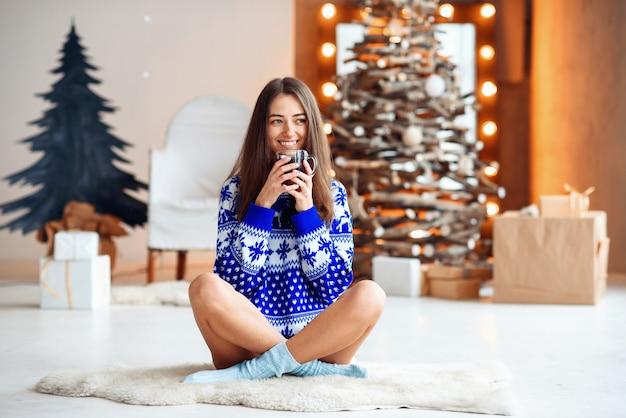 Linda garota sorridente na camisola quente do ano novo senta-se em um tapete branco quente Foto Premium