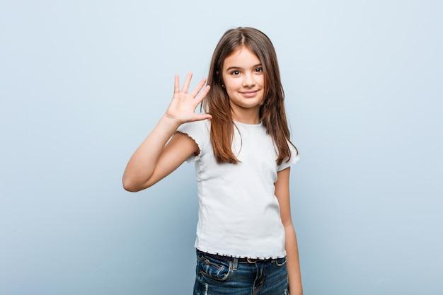 Linda garota sorrindo alegre mostrando número cinco com os dedos Foto Premium
