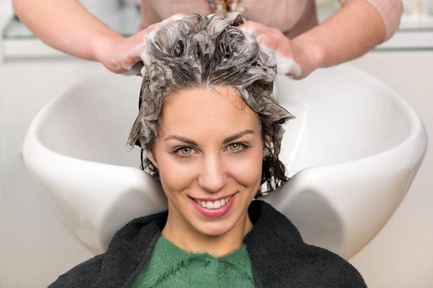 Linda garota, tendo o cabelo lavado no salão Foto Premium
