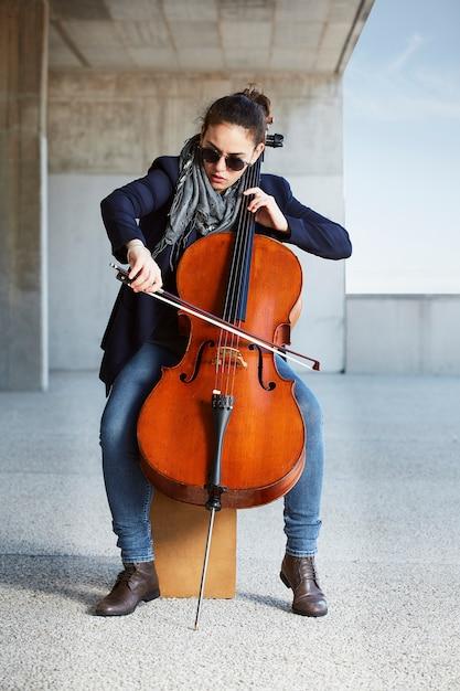 Linda garota toca violoncelo com paixão em um ambiente concreto Foto gratuita