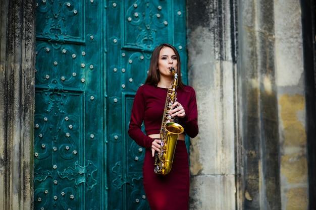 Linda garota tocando saxofone Foto Premium