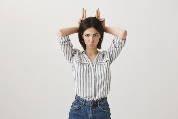 Linda garota tola mostrando chifres acima da cabeça e parecendo atrevida Foto gratuita