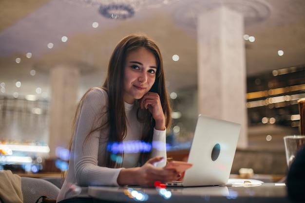 Linda garota trabalhando no laptop em um café moderno Foto gratuita
