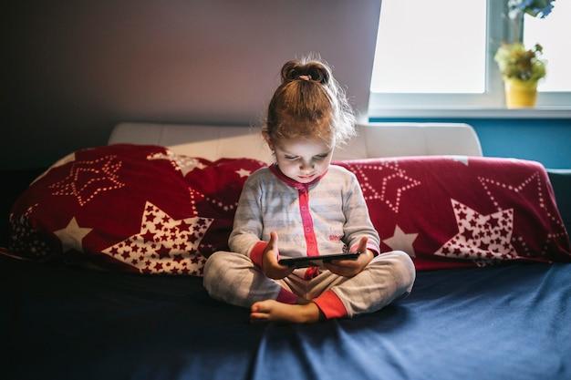 Linda garota usando smartphone na cama Foto gratuita