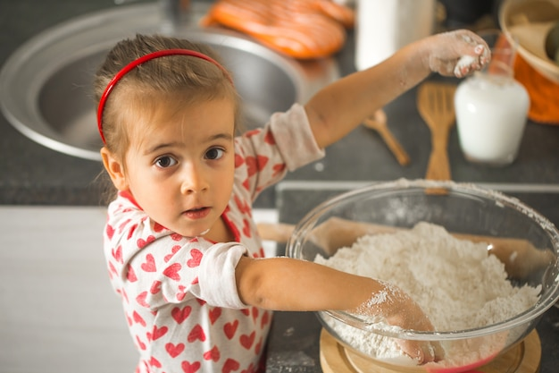 Linda garotinha baker na cozinha Foto gratuita