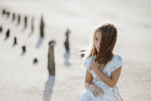 Linda garotinha caucasiana no chão seco nas férias de verão sozinha em vestido branco está olhando para o lado, infância feliz Foto gratuita
