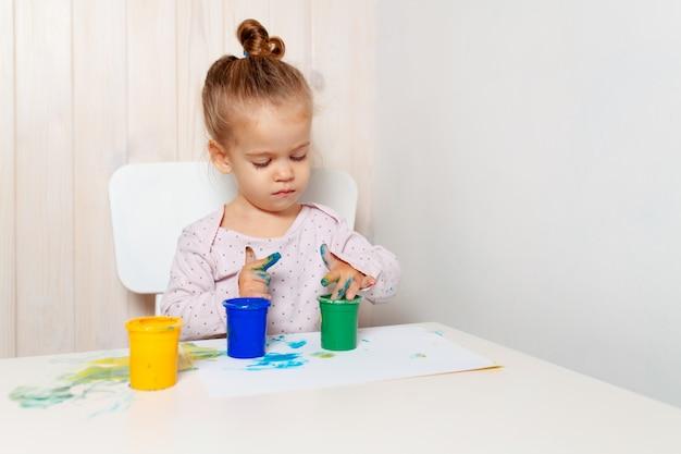 Linda garotinha desenha com tintas de dedo em uma folha de papel branca Foto Premium