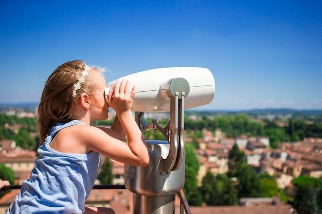 Linda garotinha olhando binóculo a moedas no terraço na pequena cidade da toscana, itália Foto Premium