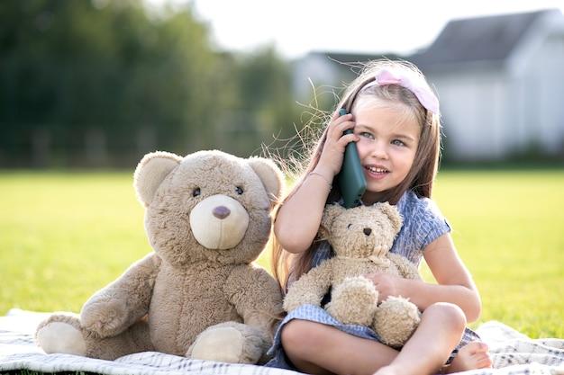 Linda garotinha sentada no parque de verão com seu ursinho de pelúcia falando no celular, sorrindo alegremente ao ar livre no verão. Foto Premium