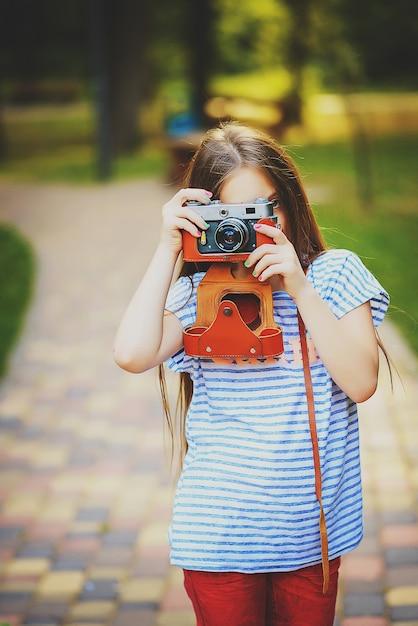 Linda garotinha tira uma foto com uma câmera vintage em uma floresta verde e ensolarada Foto Premium