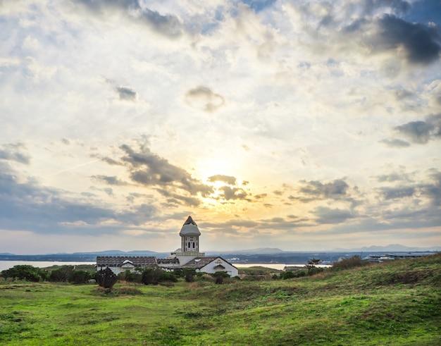 Linda igreja católica na manhã com o nascer do sol e o céu azul em seopjikoji mount jeju island, coréia do sul Foto Premium