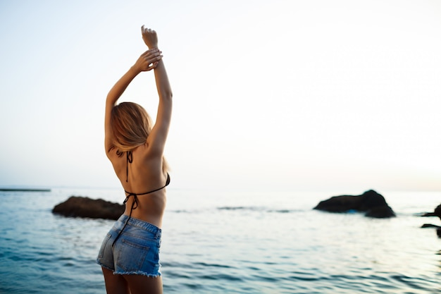 Linda jovem baseia-se na praia de manhã Foto gratuita