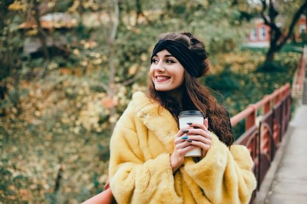 Linda jovem bebe café em um copo na rua, ri e sorri Foto gratuita