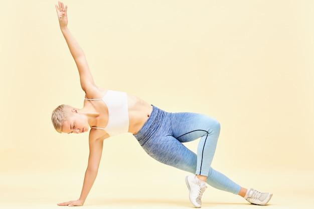 Linda jovem loira com corpo musculoso lindo trabalhando em equilíbrio e força fazendo pose de prancha lateral ou vasisthasana levantando um braço, tentando manter o equilíbrio o maior tempo possível Foto gratuita