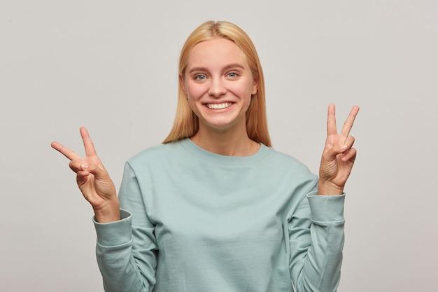 Linda jovem loira se diverte, sorri, mostra o sinal da vitória da paz com os dedos das duas mãos Foto gratuita