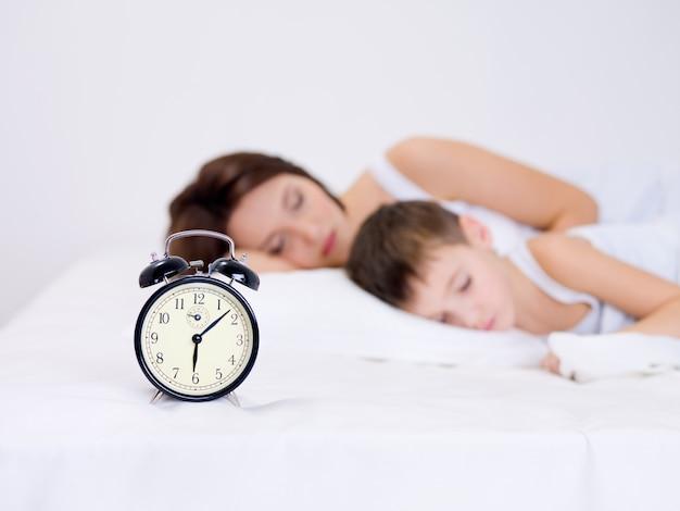 Linda jovem mãe e seu filho pré-escolar dormindo com despertador Foto gratuita