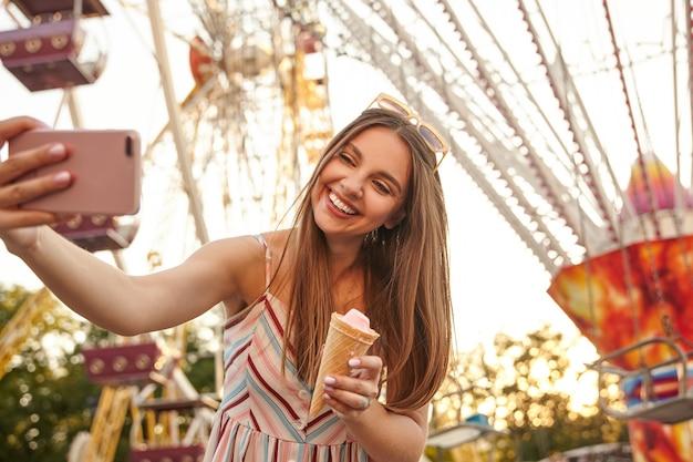 Linda jovem morena de cabelos compridos com vestido de verão romântico posando sobre as atrações enquanto faz uma selfie com seu telefone celular, mantendo a casquinha de sorvete na mão e sorrindo alegremente Foto gratuita
