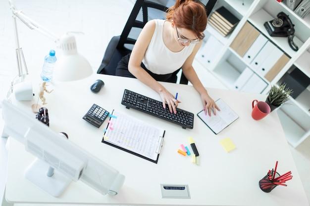 Linda jovem no escritório trabalhando com documentos, calculadora, bloco de notas e computador Foto Premium